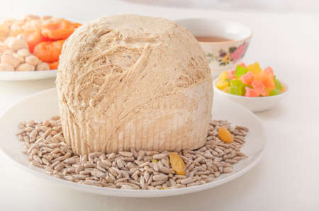 Sunflower halva on a white plate against the background of pistachios, peanuts, candied fruits, raisins, dried apricots and Asian cups for tea on a white table. Eastern sweets. Close-up 스톡 콘텐츠