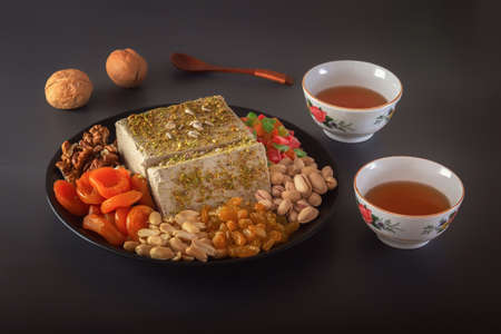 Sunflower halva sprinkled with crushed nuts and raisins on a black plate with pistachios, peanuts, dried apricots, candied fruit syrup and Asian tea cups on a dark background. Eastern sweets. 스톡 콘텐츠