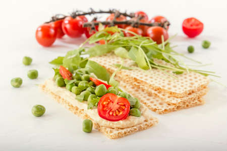 Crispy low calorie wheat crackers with green peas, arugula, microgreens and tomatoes on a white wooden table. Close-up