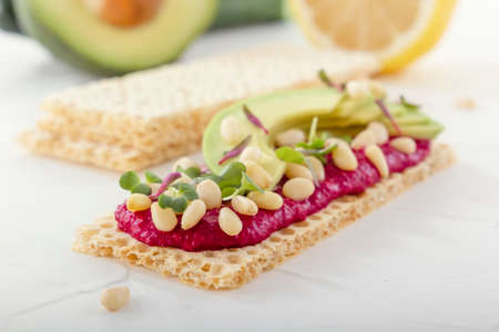 Crispy low calorie wheat crackers with beetroot hummus, pine nuts and avocado slices on a white wooden table. Close-up