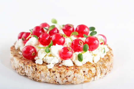 Puffed exploded wheat grains with curd cheese, red currants and microgreens on a light wooden background. Close-up