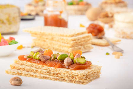 Crispy low-calorie wheat crackers with pistachios and candied fruits on a thin layer of apricot jam on a white table against a background of oriental sweets. Close-up 스톡 콘텐츠