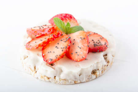 Puffed exploded wheat grains with white chocolate frosting with chopped strawberries, chia seeds and mint leaves on a light wooden background. Close-up