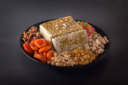 Sunflower halva sprinkled with crushed nuts and raisins on a black plate with pistachios, peanuts, dried apricots, candied fruit syrup and on a dark background. Eastern sweets. Copy space