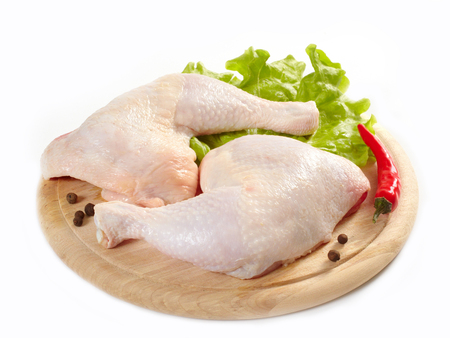 Raw chicken on a wooden cutting board with spices isolated on white