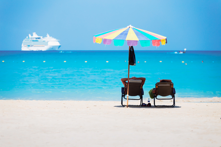 Two chairs on white sandy beach