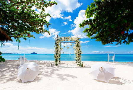 Wedding arch on the white sandy beach. two chairs and umbrellas