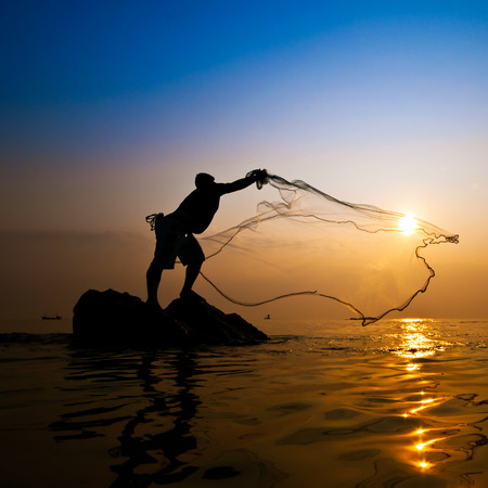 Fisherman with net at sunset 写真素材