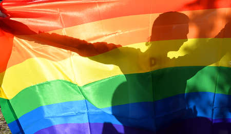 Rainbow colored flag of LGBT society and shadow of gay behind it