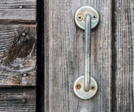 door handle: Metal handle on old grey wood door