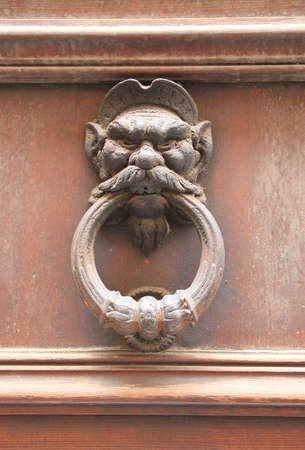 deity: Old roman door knocker in a form of men deity with beard, mustache, and ring in the teeth Stock Photo