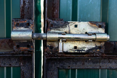 Old rusty metal brass latch roughly velded to green metal gates closeup