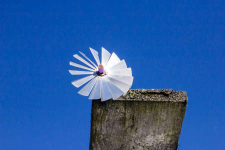 rotates: handmade stainless steel Windmill ratchet on edge of old board on blue sky background in country