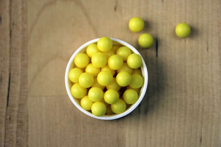 dragee: handful of many round yellow vitamin C dragee pills closeup on wood background
