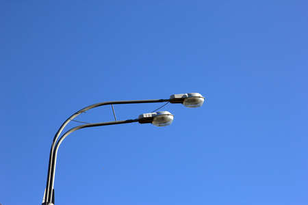 steel head: double head of steel streetlight closeup on blue sky background, Moscow, Russia
