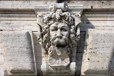 escultura romana: escultura de piedra medieval romano en la pared del edificio en forma de cabeza de león con la lengua fuera, Roma, Italia