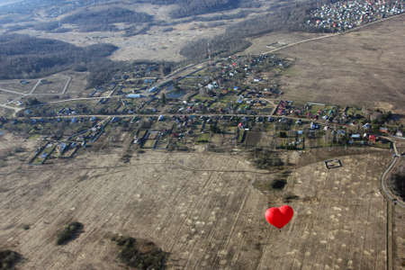birds eye view: red balloon in the shape of red heart hovers over the terrain - fields, village and forests in morning - birds eye view
