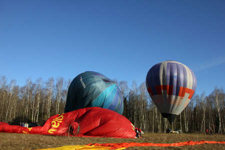 inflating: red ballon lies on the ground - process of inflating the balloons on a field with blue morning sky as a background, Dmitrov, Russia
