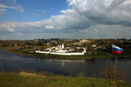 other side of: beautiful panoramic view from hill to old ancient orthodox white monastery on the other side of river and russian state flag on the hill, Staritsa, Russia Stock Photo