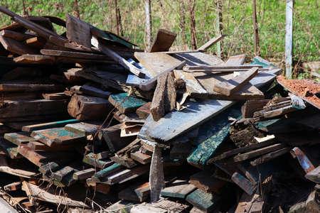 house demolition: A pile of debris and old broken wooden boards after demolition of the house