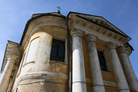 portico: old orthodox church in classical style with classical white portico and yellow shabby walls and cross on top