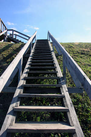 wooden railings: grey long wooden staircase with wooden railings on the green hill, view from the bottom up and blue sky