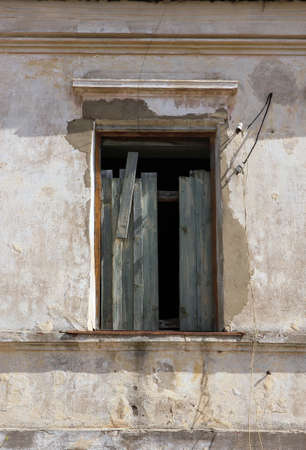 without window: old ruined destroyed window without frame in old building is chock-full of boards