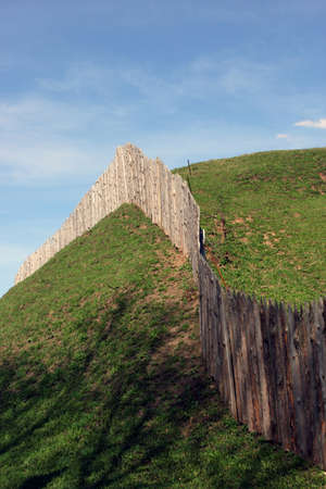 palisade: the wooden palisade on the green grass shaft of the ancient fortress and city and blue sky as a background, Torzhok, Russia