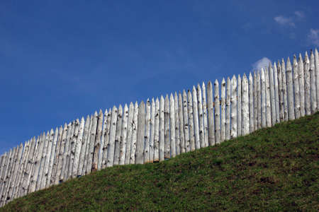 palisade: the wooden palisade on the green grass shaft  and blue sky as a background, Torzhok, Russia