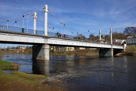 across: Old metal pedestrian bridge across the river Tvertsa, Torzhok, Russia