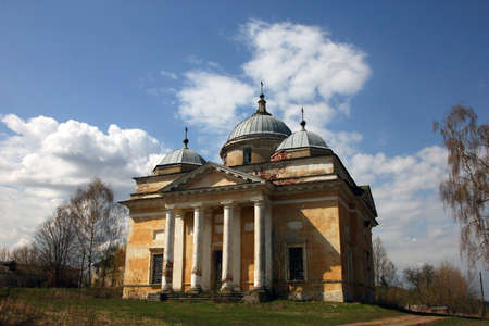 portico: old orthodox church in classical style with classical white portico and yellow shabby walls and grey dome