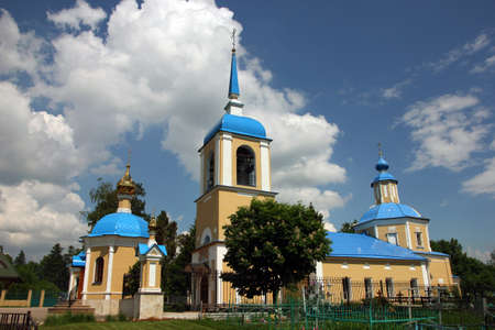dome type: beautiful landscape with old russian orthodox church in classical style with yellow walls and blue roof and dome and belfry in village Stock Photo