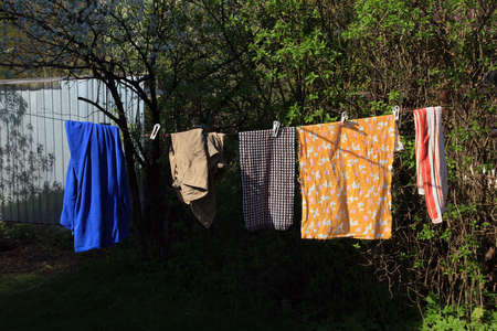 countrylife: washed clean linen with clothespines drying on the rope outside in the village Stock Photo