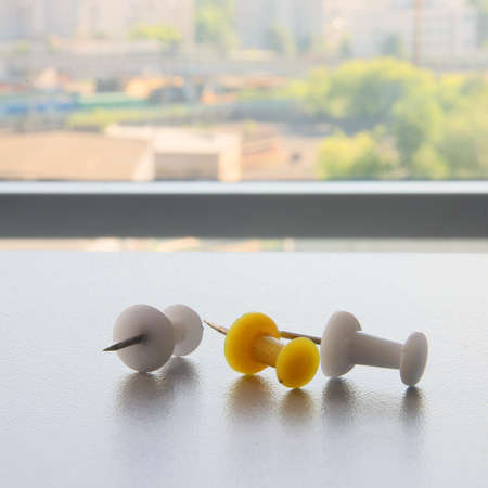 yellow pushpin: three color plastic white and yellow pushpin with metal needle on white office table closeup