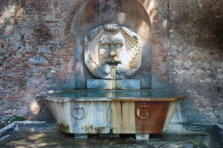 bathtub old: old ancient roman fountain with marble mask of face poseidon and marble bathtub from roman thermae