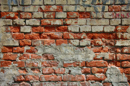 dilapidated wall: texture of old dilapidated shabby brickwork of red brick wall foreground closeup Stock Photo