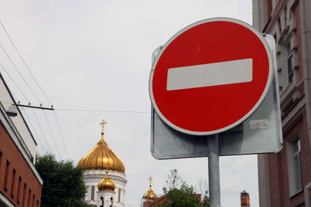 atheist: metal round red road stop sign with white stripe in the background of golden dome of orthodox church Stock Photo