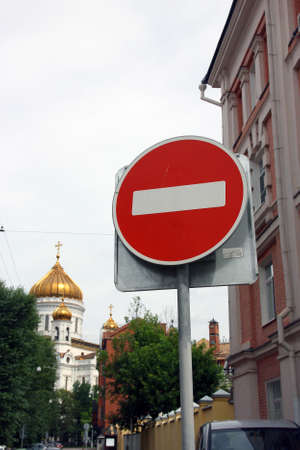 oppose: metal round red road stop sign with white stripe in the background of golden dome of orthodox church Stock Photo
