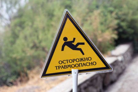 hombre cayendo: triangular yellow sign with inscription caution traumatic and image of falling man closeup