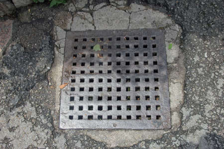 cast metal type: old rusty square cast iron manhole cover of storm sewer on asphalt road Stock Photo