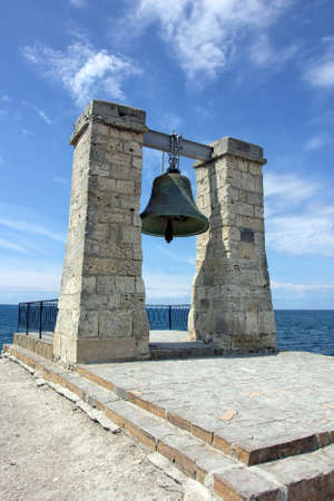bell bronze bell: old large green bronze bell hanging on stone arch on the coast of Black sea in Crimea