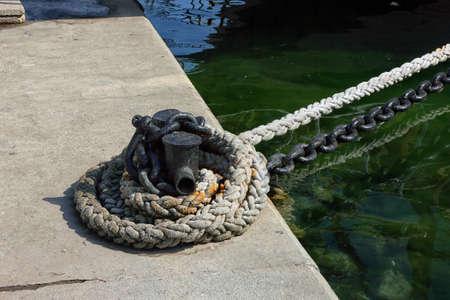 black metal iron mooring bollard with mooring line and chain and green sea water