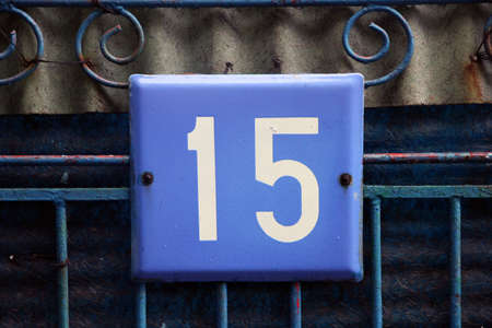 fifteen: blue square metal number plate with the number fifteen on blue metal bar