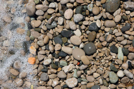 beautiful wet round colored sea pebbles on pebble beach with bubbling sea water closeup Stock Photo