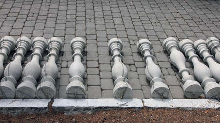 beautification: grey concrete balusters lying on sidewalk installation-ready