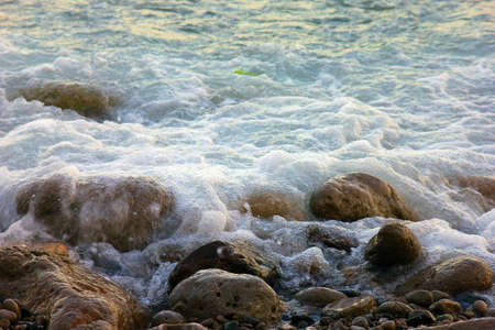 foaming: sea surf with turquoise wave on crimean pebble beach in summer season Stock Photo