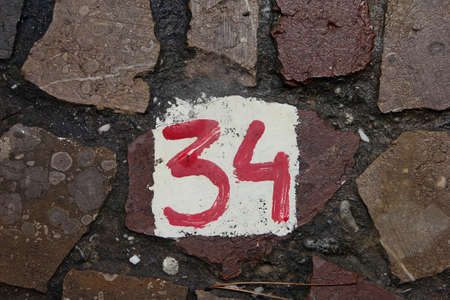 34: The number 34 painted with red paint on white background on wall of stone masonry