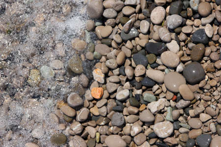 big slick: beautiful wet round colored sea pebbles on pebble beach with bubbling sea water closeup Stock Photo