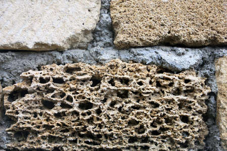 dilapidated: old dilapidated shabby coquina rock in masonry of wall foreground closeup in Crimea