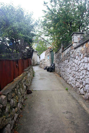 fense: typical small street with stone fense with rubble in crimean town Simeiz Stock Photo